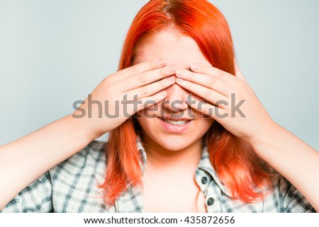 close-up of a bright red-haired girl closes eyes with her hands tired