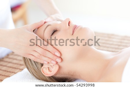 Close-up of a bright woman receiving a head massage in a Spa center - stock photo