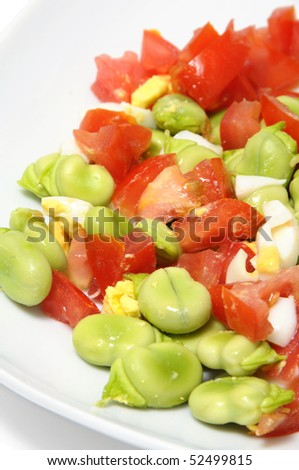 close up of a broad beans salad with tomato and boiled egg - stock photo