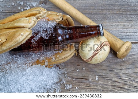 Close up of a brown bottled beer with crushed ice inside of baseball glove on rustic wood with ball and bat   - stock photo