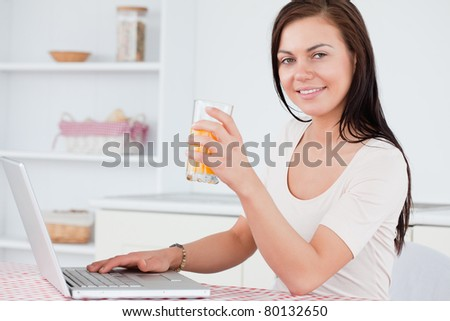 Close up of a brunette using her laptop and drinking juice in her kitchen