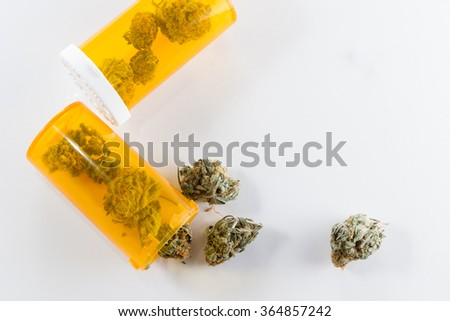 Close up of a bud of cannabis inside of an orange prescription bottle over a white background - stock photo