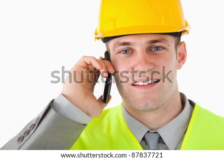 Close up of a builder making a phone call against a white background