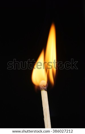 Close-up of a burning matchstick, isolated on black background. - stock photo