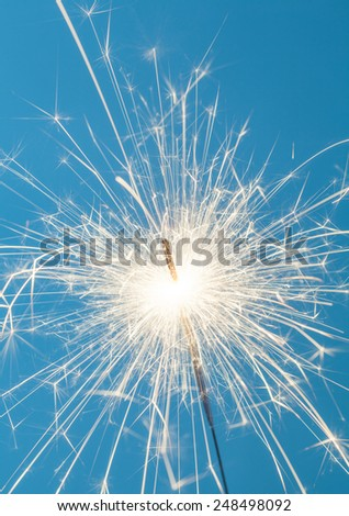 Close up of a burning sparkler on a blue background - stock photo