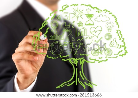 Close up of a business man hand drawing ecology concept icons, grouped inside green tree. - stock photo