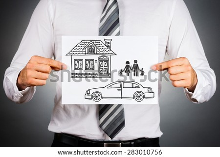 Close up of a business man,holding white card with house,car and family drawing inside.Isolated against grey background. - stock photo