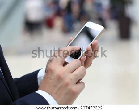 Close up of a business man using mobile smart phone - stock photo