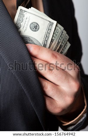 Close up of a business mans hand hiding money in his suit jacket pocket. - stock photo