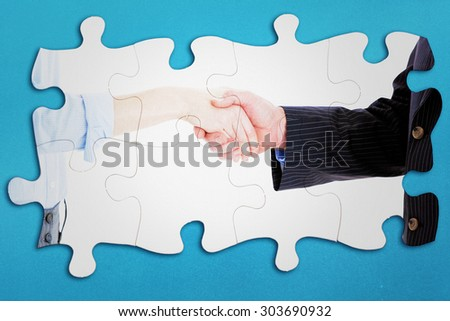 Close up of a business people closing a deal against blue background