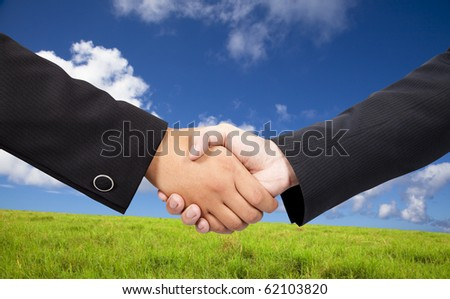 Close-up of a business people shaking hands against blue sky and green background - stock photo