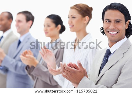 Close-up of a business team smiling and applauding while looking towards the left side except for one against white background - stock photo