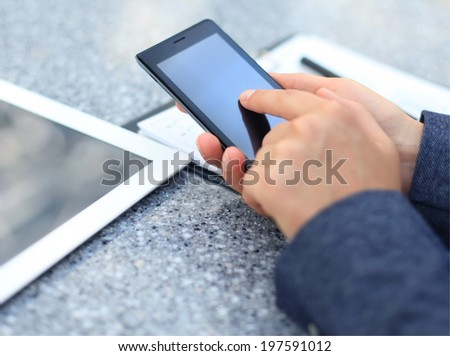 Close up of a business woman using mobile smart phone  - stock photo