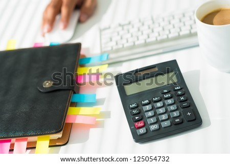 Close-up of a business workplace with an organizer, a calculator and a cup of coffee - stock photo