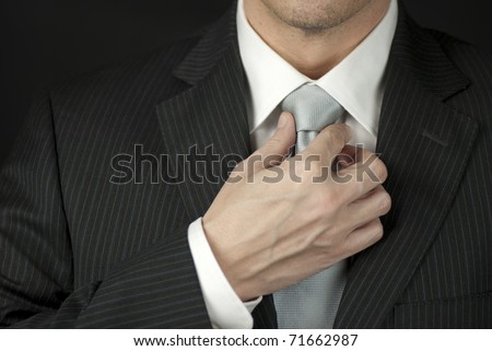 Close-up of a businessman adjusting his tie. - stock photo