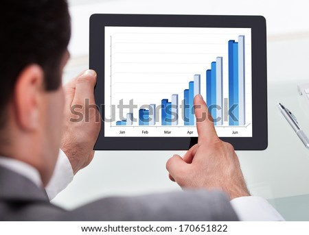 Close-up Of A Businessman Analyzing Graph On Digital Tablet - stock photo
