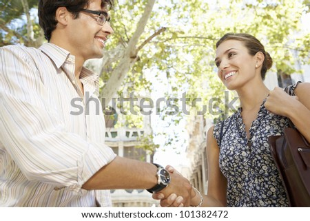 Close up of a businessman and businesswoman shaking hands in the city, smiling. - stock photo