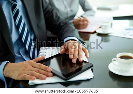 Close-up of a businessman at his workplace with a newspaper, cup of coffee and a tablet computer