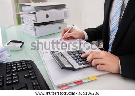 Close-up Of A Businessman Calculating Invoice With Calculator - stock photo