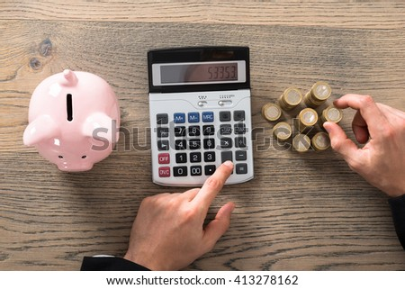 Close-up Of A Businessman Counting Coins Using Calculator At Desk In Office - stock photo