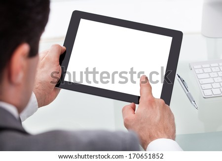 Close-up Of A Businessman Holding Digital Tablet On Desk - stock photo