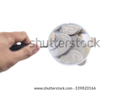 Close-up Of A Businessman Holding Magnifying Glass Over Coins On white background. - stock photo
