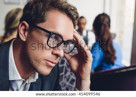 Close up of a businessman looking stressed. He has his hand on his head and there are other people in the background. - stock photo