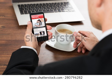 Close-up Of A Businessman Reading News On Cellphone While Having Coffee - stock photo