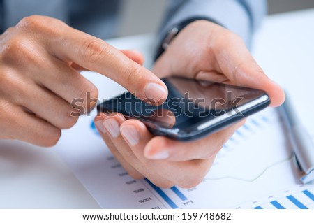 Close Up Of A Businessman's Hand Over Documents Using Smart Phone - stock photo