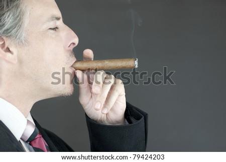 Close-up of a businessman smoking a cigar, side view. - stock photo
