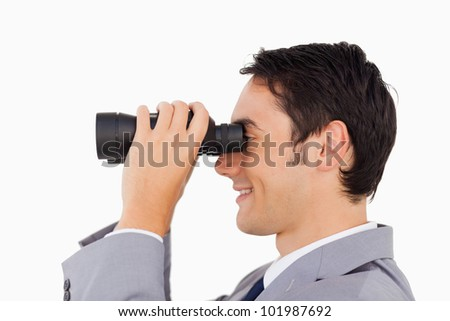 Close-up of a businessman using binoculars against white background
