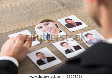 Close-up Of A Businessman Viewing Candidates Through Magnifying Glass At Desk In Office - stock photo