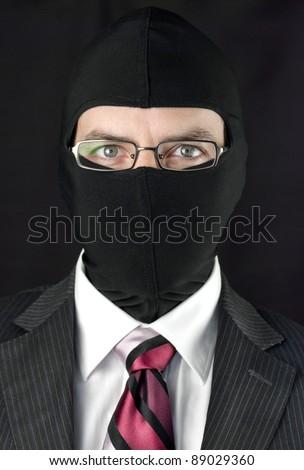 Close-up of a businessman wearing a balaclava looking at camera - stock photo