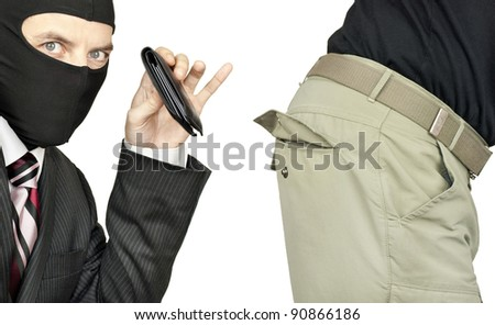 Close-up of a businessman wearing a balaclava picking the trouser pocket of a middle class man. - stock photo