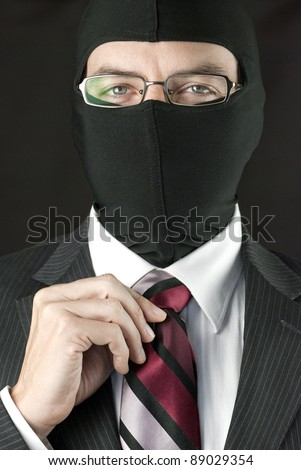 Close-up of a businessman wearing a balaclava straightening his tie.