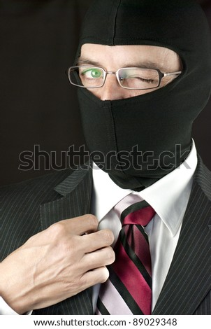 Close-up of a businessman wearing a balaclava winking at camera - stock photo