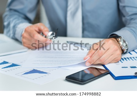Close Up Of A Businessman With Documents Working At His Desk - stock photo