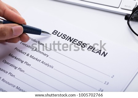 Close-up Of A Businessperson's Hand Making Business Plan