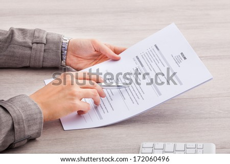 Close-up Of A Businesswoman At Desk Holding Resume - stock photo
