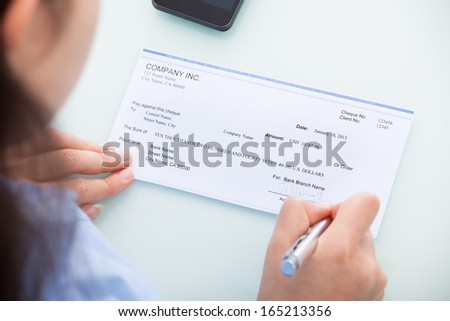 Close-up Of A Businesswoman Filling Blank Cheque At Desk - stock photo