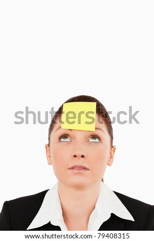 Close up of a businesswoman looking at the note on her forehead against a white background - stock photo