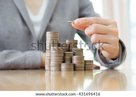 Close-up Of A Businesswoman Making Stack Of Coins