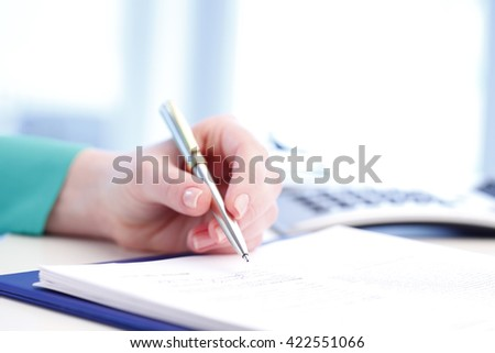 Close-up of a businesswoman sign the contract while sitting at desk in office. - stock photo