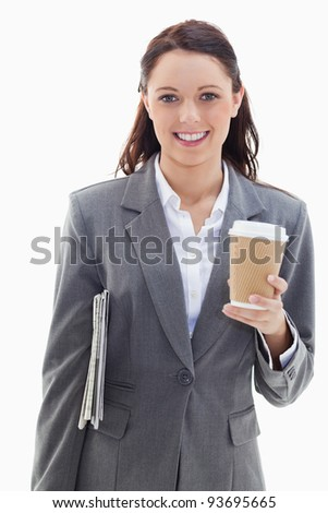 Close-up of a businesswoman smiling with a newspaper under her arm and holding a coffee against white background - stock photo