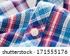 Close up of a button on a tartan shirt with shallow depth of field - stock photo
