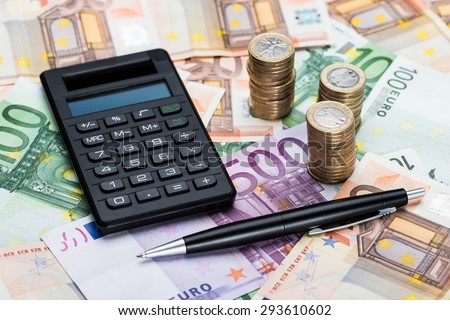 Close-up Of A Calculator And Pen With Stacked Coins On Euro Banknotes - stock photo