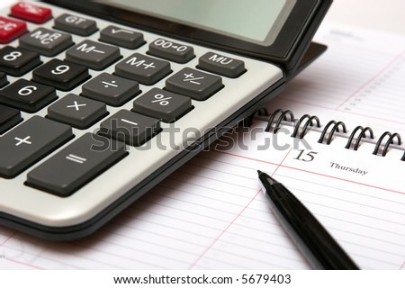 Close up of a calculator, organizer and pen.
