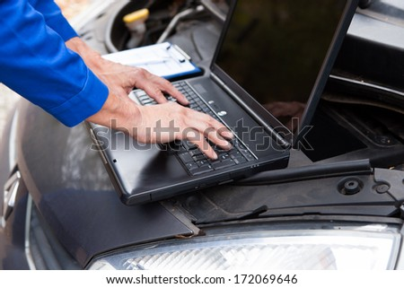 Close-up Of A Car Mechanic Using Laptop To Repair Car - stock photo