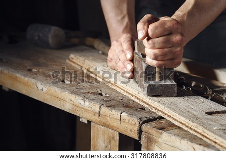 Close up of a carpenter planing a plank of wood with a hand plane - stock photo