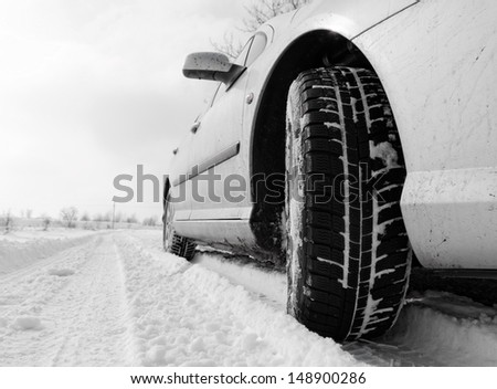 Close up of a cars tires on a snowy road - stock photo
